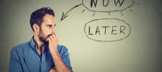Now or later. Man thinking looking worried anxious making up his mind